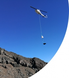 A helicopter delivers equipment to a high-altitude remediation site on Mount Ruapehu